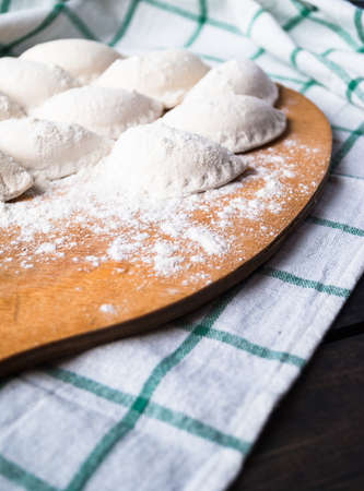 Raw dumplings sprinkled with flour on a cutting board and a striped towel. Close up Stockfoto