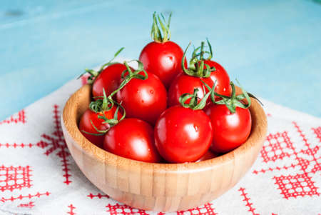 Ripe red cherry tomatoes in a bowl on a white kitchen towel with red pattern 写真素材