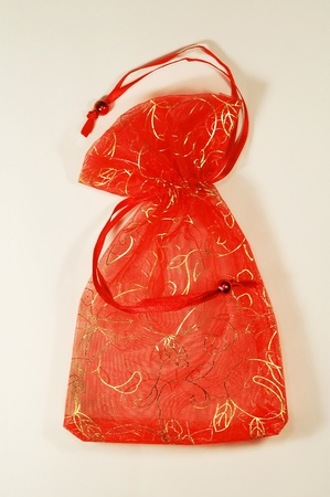 Small shiny red present bag with a rope