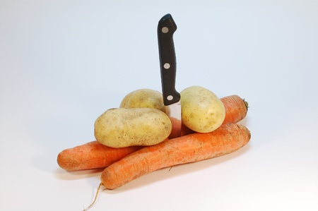 Vertically positioned knife with few carrots and potatoes