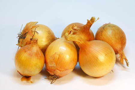 Close view of six fresh and clean onions.