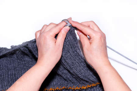 A woman knitting with gray wool, a close-up of her hand