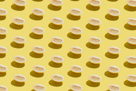Creative bright pattern made with fresh melon on yellow background. Minimal sunlit isometric.