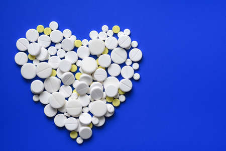 Round tablets arranged abstract isolated on blue color background. Pills for design. Concept of health, healthy lifestyle. Copy space for advertisement. Pills heart shape