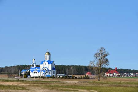 Die Landschaft der weißen Kirche steht voll am Rande des Dorfes im Frühjahr
