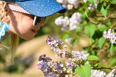 A girl in the park smells lilac flowers on a tree. Allergy to pollen. The concept of childhood and holiday