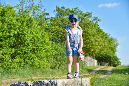 A little girl is standing on an old concrete block, crying, afraid of heights, fear. Little girl enjoying nature. Outdoor playing Standard-Bild - 103334188