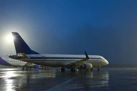 A passenger plane takes off from the airport runway at night. Aircrafr front view.