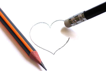 Washing on pencil erases the painted heart. Simple pencils symbolize ruined love Фото со стока
