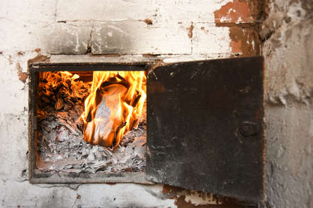 Burning fire paper, letters in indoor home interior fireplace with detail closeup of orange
