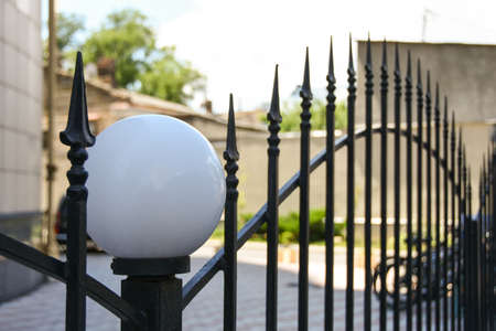 Protection of the courtyard of an apartment building with steel fence with lanterns