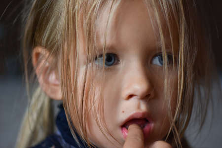 Portrait of sad romantic little girl with big blue eyes and a finger in her mouth from Eastern Europe, close-up, dark background
