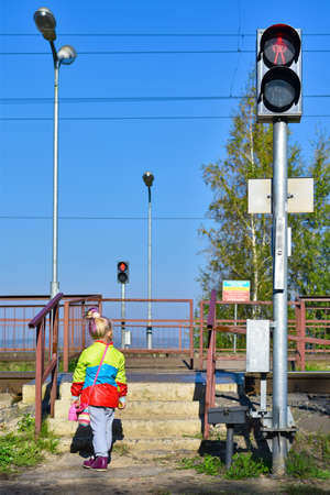 Child is standing on an unregulated railway crossing in front of a red traffic light. Imagens