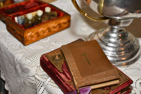 Bible lies on the table with the cup in the church before the rite of baptism Stock Photo