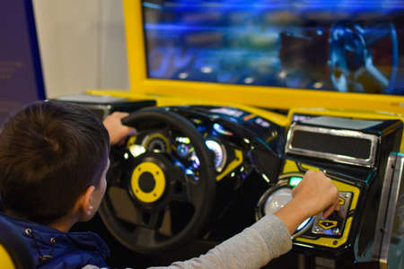 Teenager plays on gaming machine simulator car in the club Stock Photo