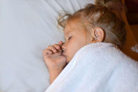 Het kind zuigt vinger in bed voor het slapengaan en tijdens de slaap