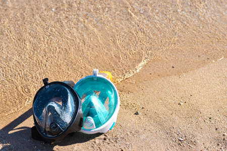 Two masks for snorkeling on sandy beach near the sea, copy Space