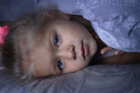 Little girl is sick and basks under the covers in bed Reklamní fotografie
