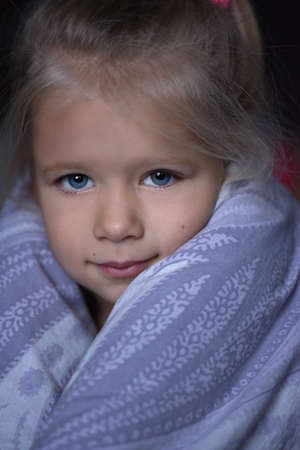Little girl is sick and basks under the covers in bed Stock Photo