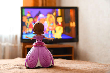 Toy doll in a pink dress is watching cartoon on the TV