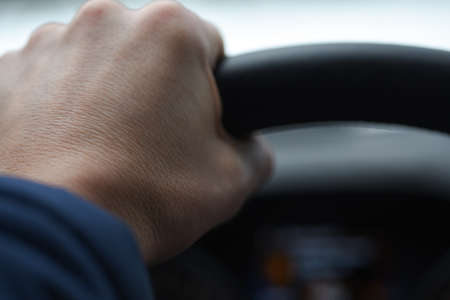 driver hand holds the steering wheel tightly, close-up