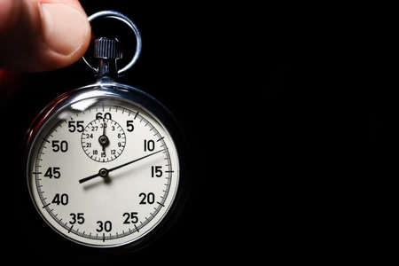 Male hand hold analog stopwatch on a black