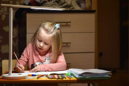 Child preschooler learns to draw and write in notebooks at home in the evening under the light from desk lamp
