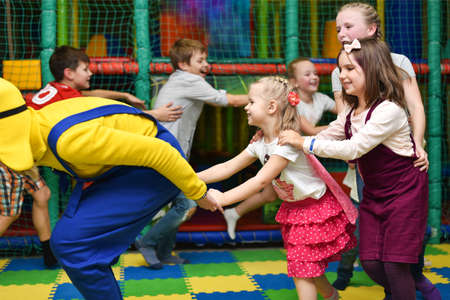 A group of children at a party play, run for the animator and hold hands.