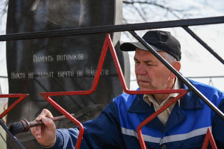 A man paints the fence on the monument to the dead Soviet soldiers in the second world war. The inscription on the monument in Russian