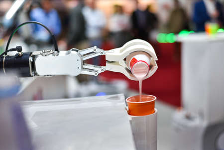 A mechanical robot with artificial intelligence pours a cocktail into a plastic cup.