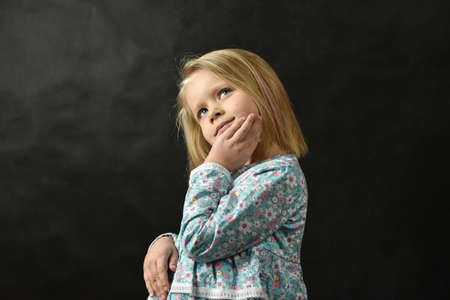 Little girl in a dress standing and dreaming on a black background.