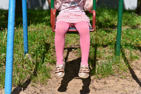 Girl legs in pink tights on a swing.