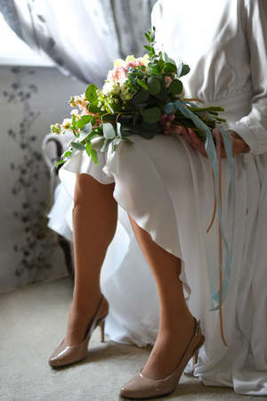 Bride with a bouquet in front of the window waiting for the groom.