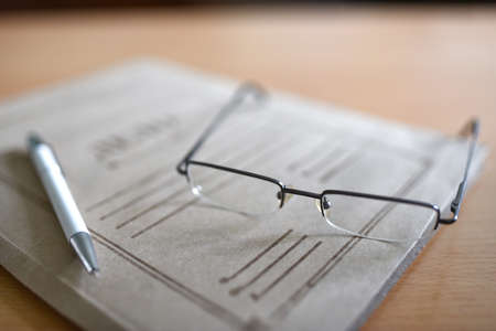 Paper folder with court documents on the table, glasses, pen. Zdjęcie Seryjne