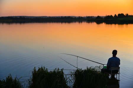 Lone fisherman fishing for a fishing rod on a lake at sunset.