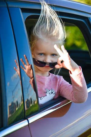 A child in sunglasses rides and smiles in a car.
