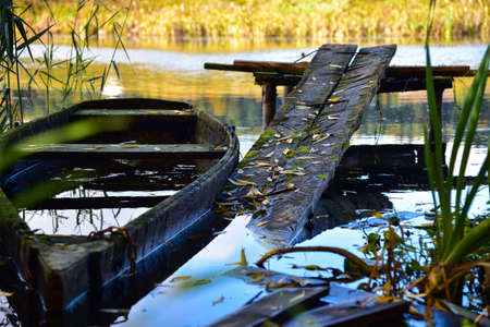 Old rotten boat on the river in autumn.