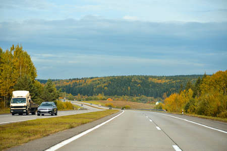 Cars ride on an autumn mountain highway.