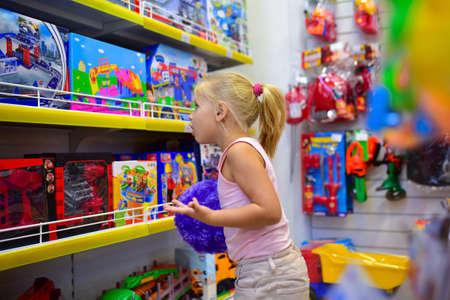 Niña mira en el escaparate de la tienda de juguetes para niños. Foto de archivo