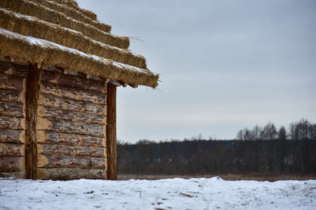 Wooden log cabin with a thatched roof in winter. Фото со стока