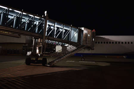People walk on the ramp to the plane at night.