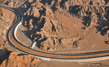 Long highway in the desert among mountains and sands, top view.