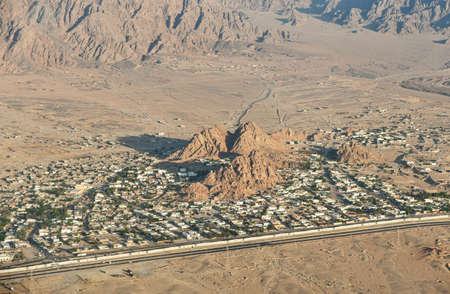 Desert city among mountains and sands, view from above.