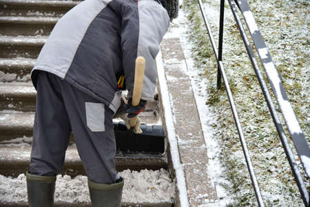 Woman cleaner shovels snow from street stairs.