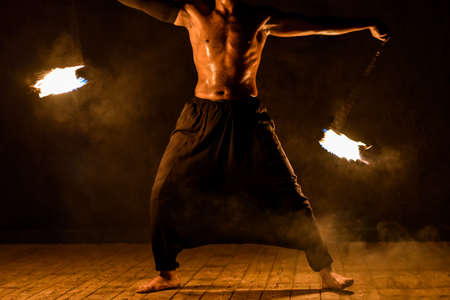 Fakir juggles fire on a black background.