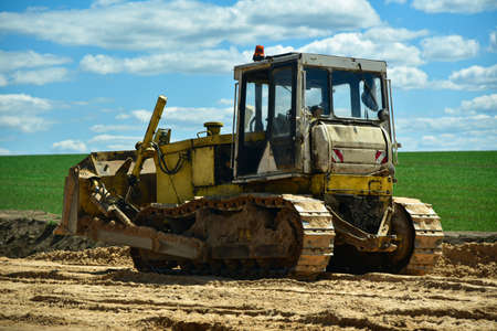 An old bulldozer removes a layer of soil in a field for the construction of a road. 스톡 콘텐츠