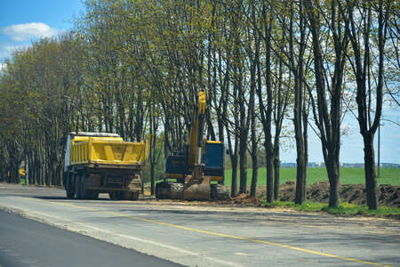 Excavator loads land on a truck during road construction.