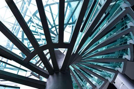 Escalier en colimaçon en métal avec marches en verre.