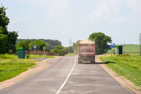 A truck carries sand and spills on the road.