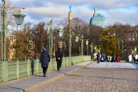 Tourists walk on the bridge in St. Petersburg.